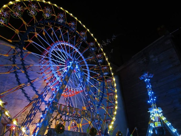 A photograph of a model of a big wheel. the model is covered in yellow lights around the outside of the wheel and blue lights on the stand.