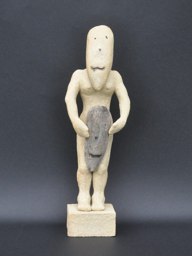 Ceramic figure holding a simple mask
