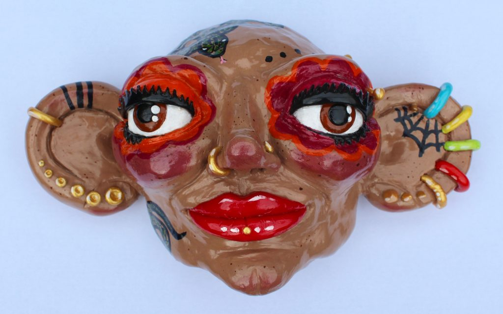 Ceramic head with brightly coloured piercings and bold make-up