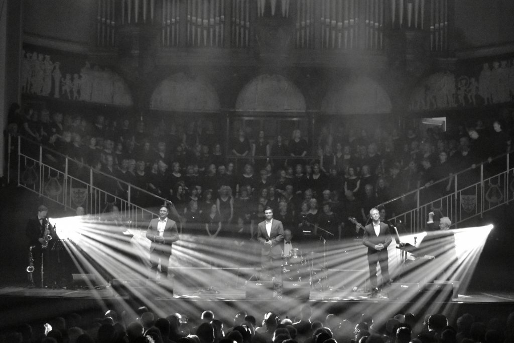 A black and white digital print of a band on stage, with dramatic spotlights