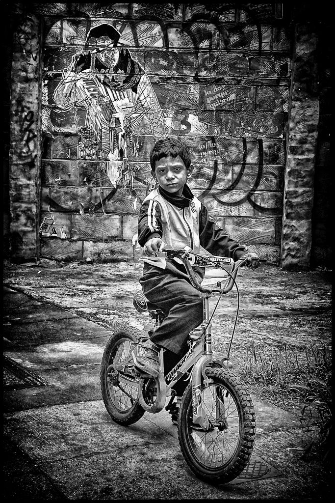 igital print of a young boy on a bike, in front of a wall of graffiti