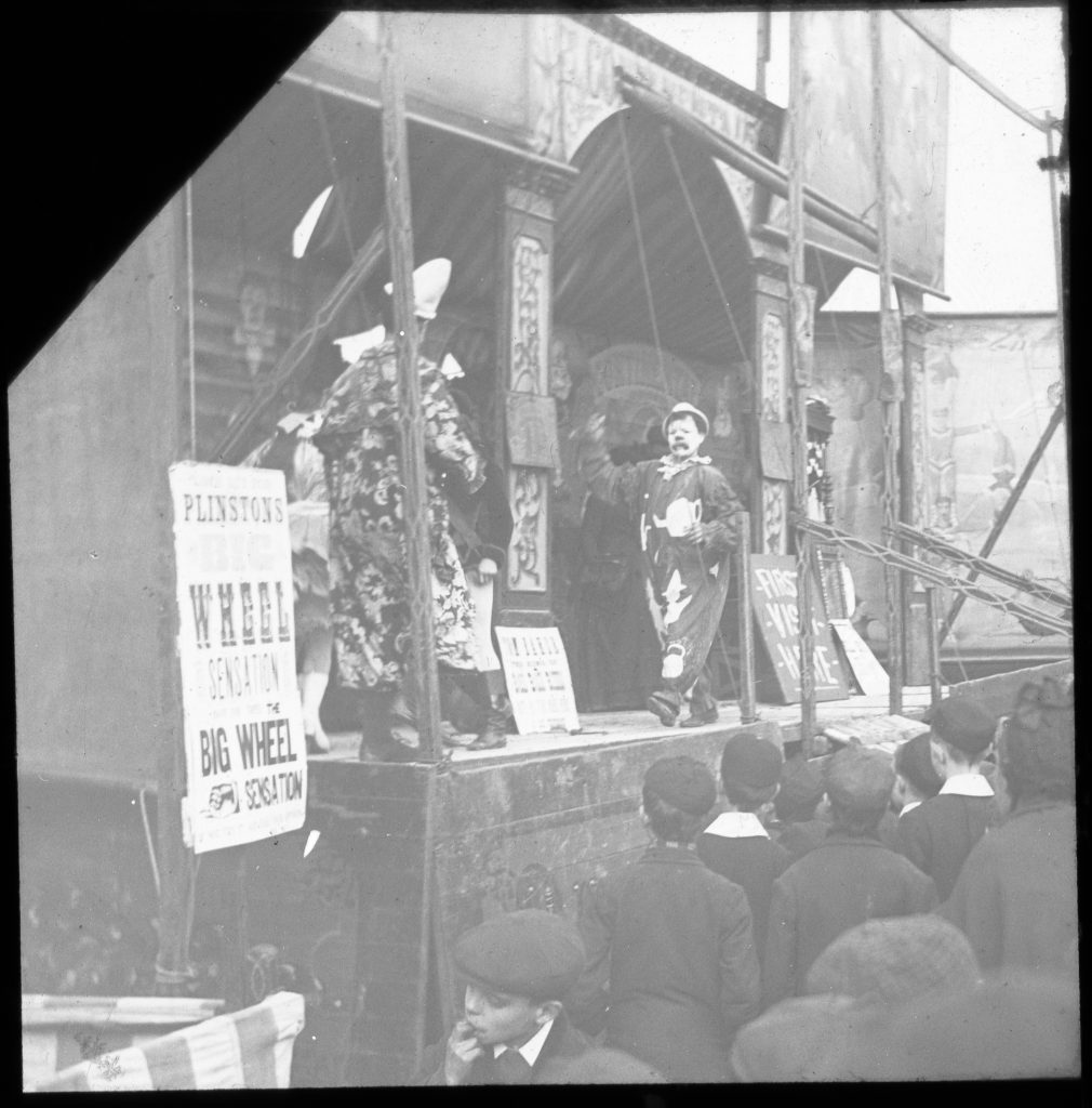 Black and white photograph of a clown at Hull Fair