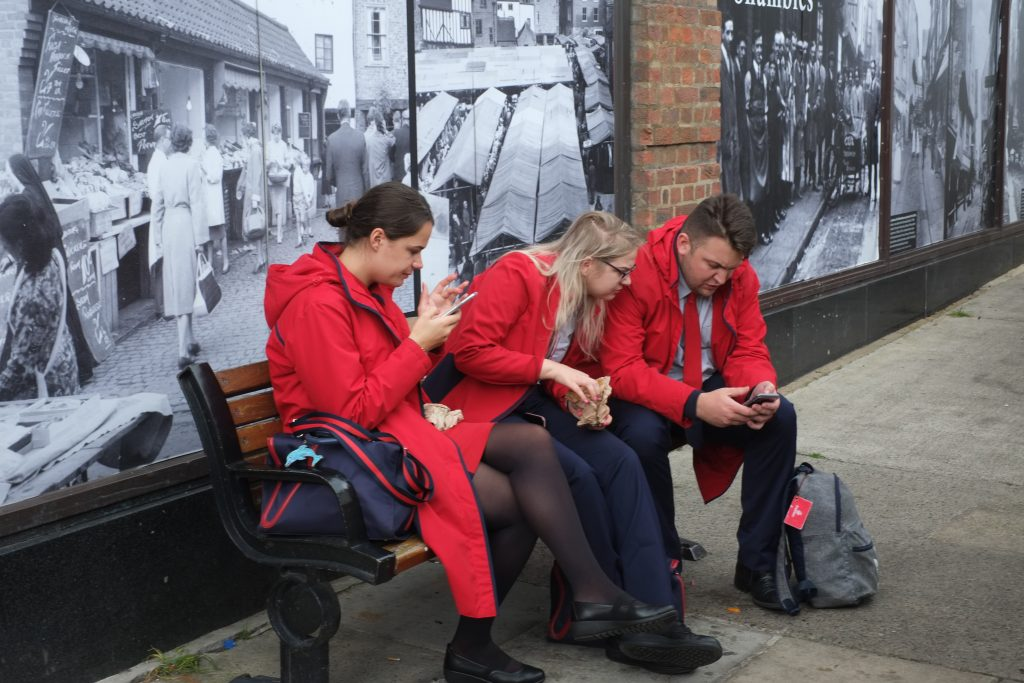 Digital print of three people sat on a bench looking at their phones