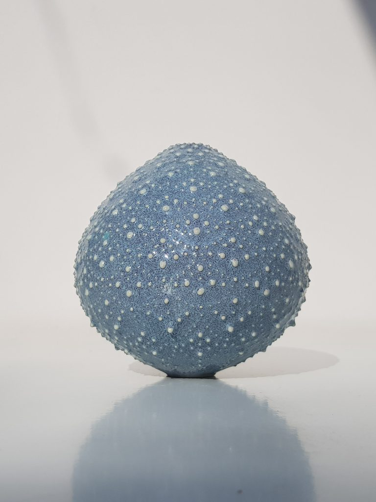 Spherical blue ceramic vase with intricate textured pattern