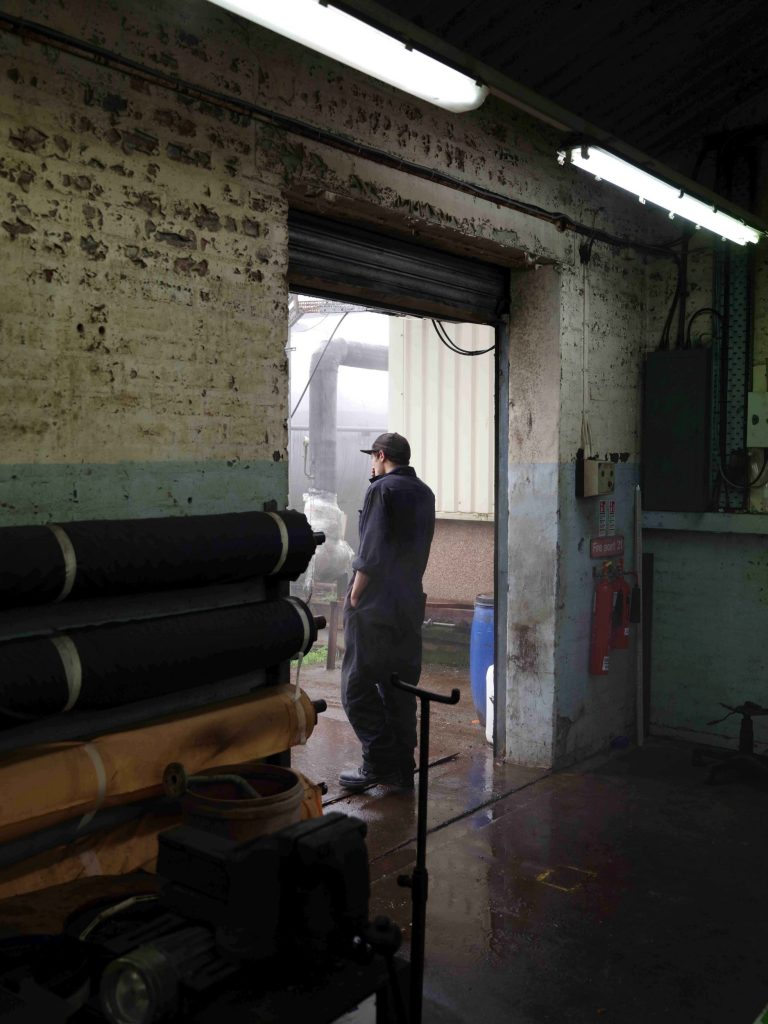 Digital print of a figure wearing a boilersuit, in a factory-like setting