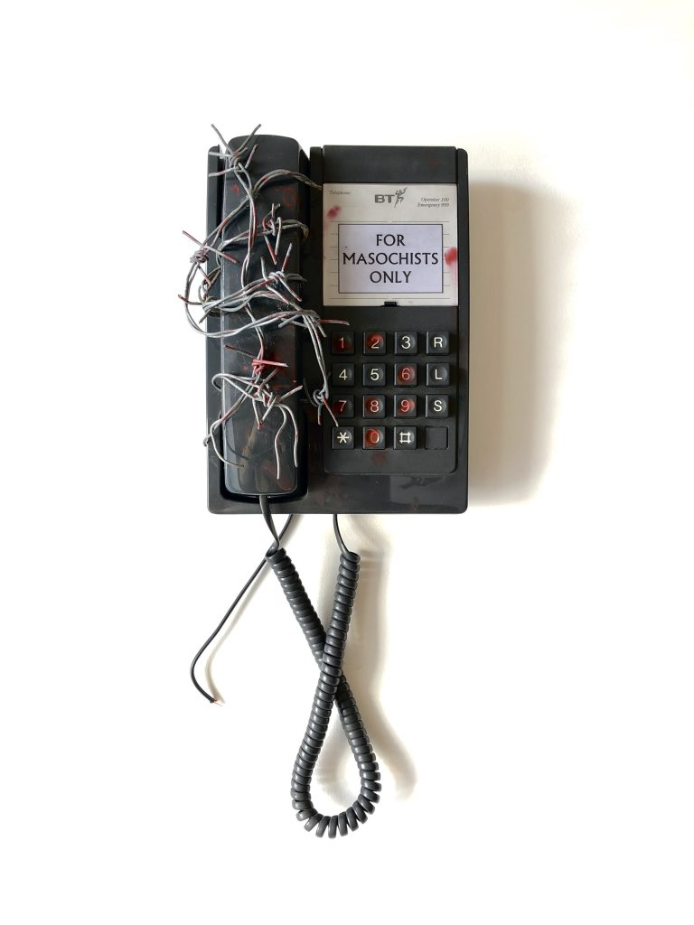 Mixed media sculpture of a wall phone wrapped in barbed wire