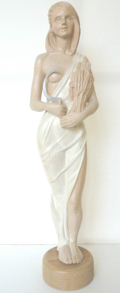 Wood sculpture of a woman in a white dress holding a sickle and corn