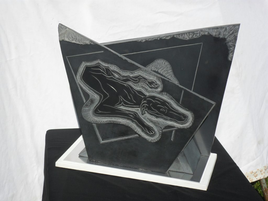 Black stone sculpture with an etched image of a dog sleeping