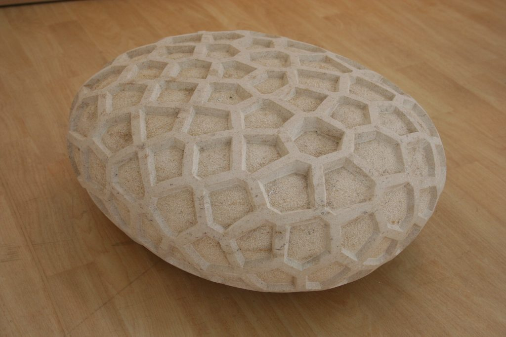 Stone sculpture with a repeated hexagonal patterned surface