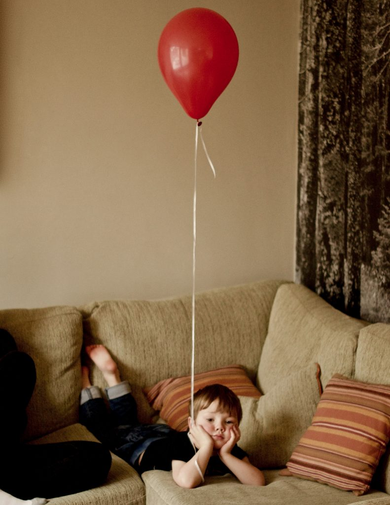 Digital print of a boy laying ona sofa holding a single red balloon