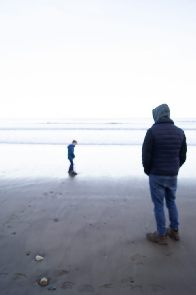 Digital print of a man and boy stood on the beach