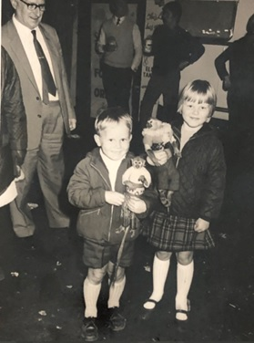 A black and white photograph of a boy and a girl at Hull Fair, both holding small monkeys.