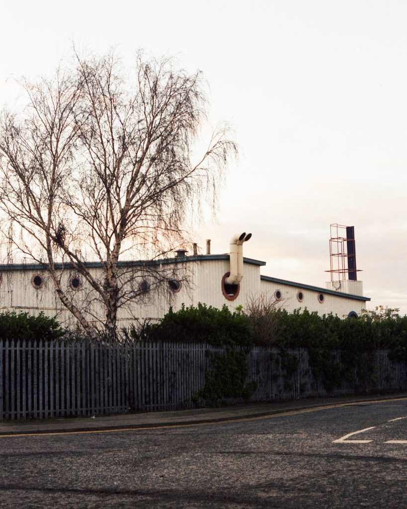 Digital print of a white industrial building behind a metal fence, with a single tree.