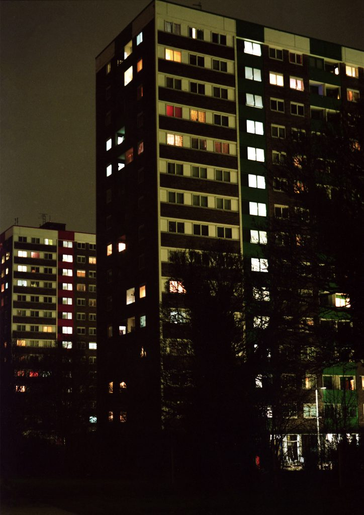 Digital print of high rise flats at night, with illuminated windows.