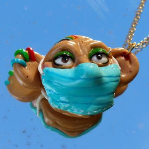 Polymer clay necklace of a face wearing a blue mask - with green eyeshadow and colourful piercings.
