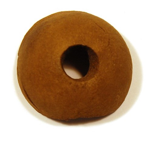 Brown, dome-shaped object with a circular hole drilled through its centre.
