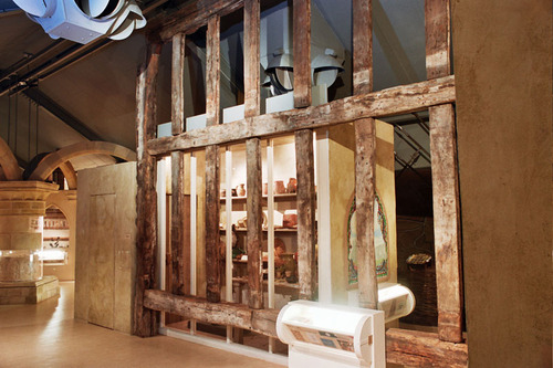 Part of a timber frame with multiple vertical posts and two horizontal beams on display in a museum gallery
