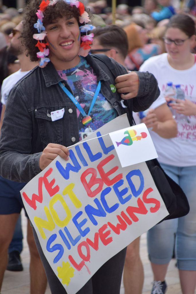 A Pride in Hull attendee holding a sign which reads, we will not be silenced love wins