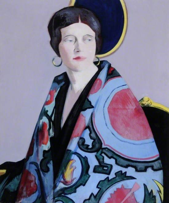 1920s. Half length portrait of fashionable young lady with two oval frames in the background; she wears a Spanish shawl; hoop earrings.