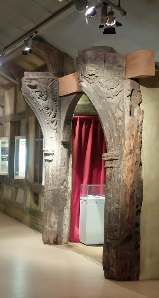 Two vertical posts on display in a museum gallery. The tops of the posts just out and are decorated with carvings.