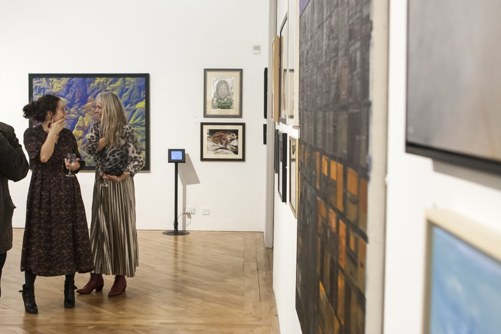 Two people stand chatting in a busy art gallery.