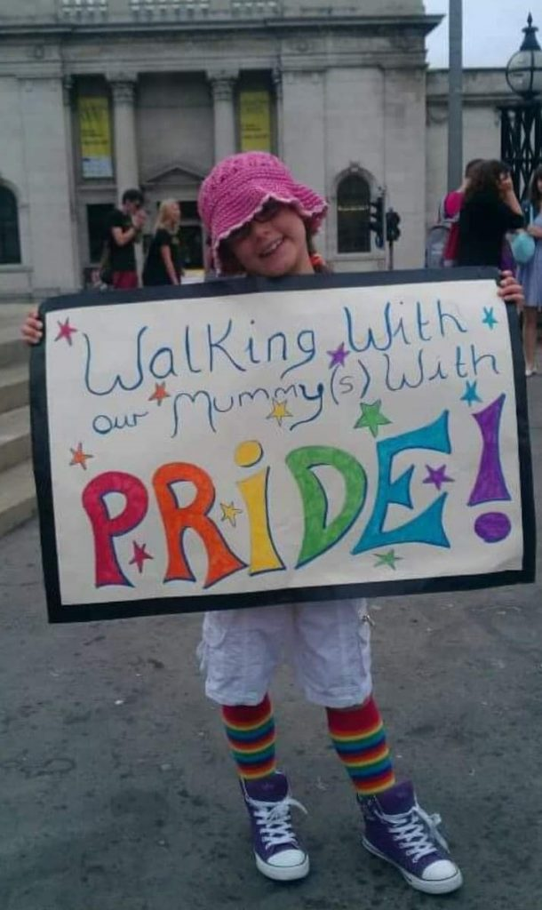 A young child at Pride in Hull holding a sign which reads, walking with our mummys with Pride.