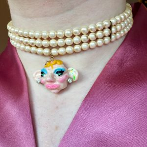 Pearl style necklace with a pendant of a face with bright makeup.