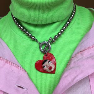 Necklace with a chunky metal chain and a red, heart-shaped pendant with a face on it.