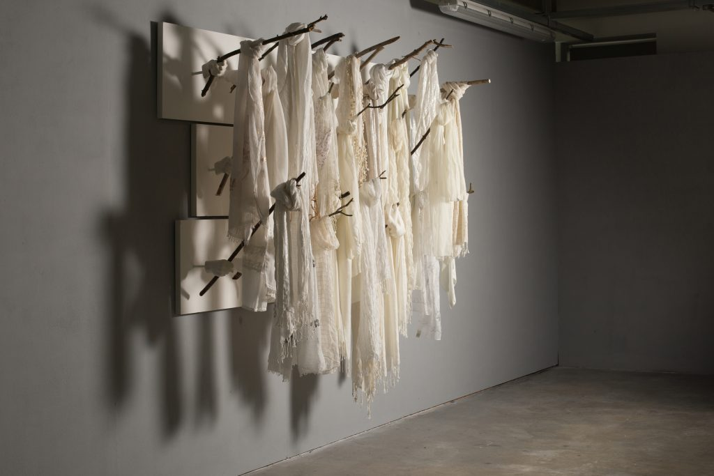 A wall-based sculpture featuring plaster cast hands holding sticks wit white scarves hanging from them.