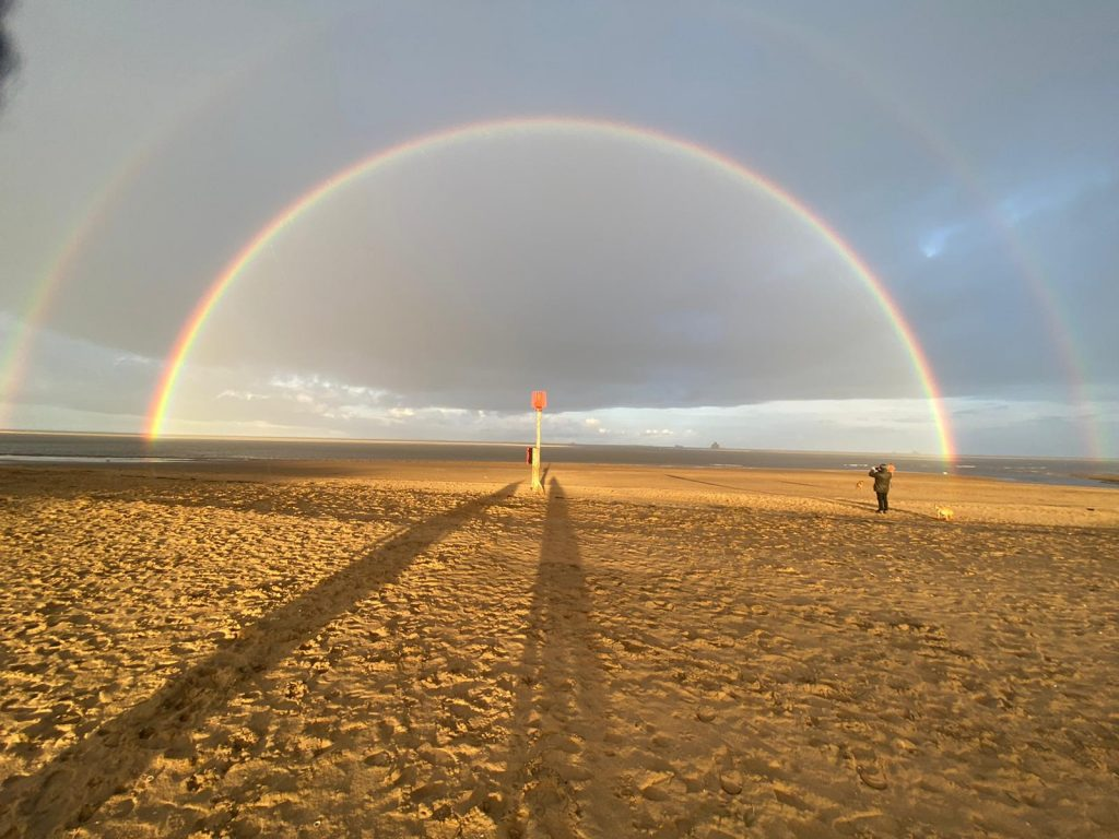 Photograph of a rainbow across a beach.