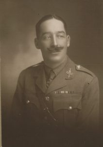 Sepia photograph of man looking slightly to the right of viewer wearing British World War One uniform.