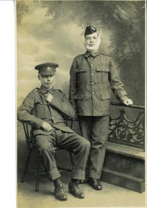 Sepia photograph of two men in World War One British uniforms, one seated, wearing bandages around chins.