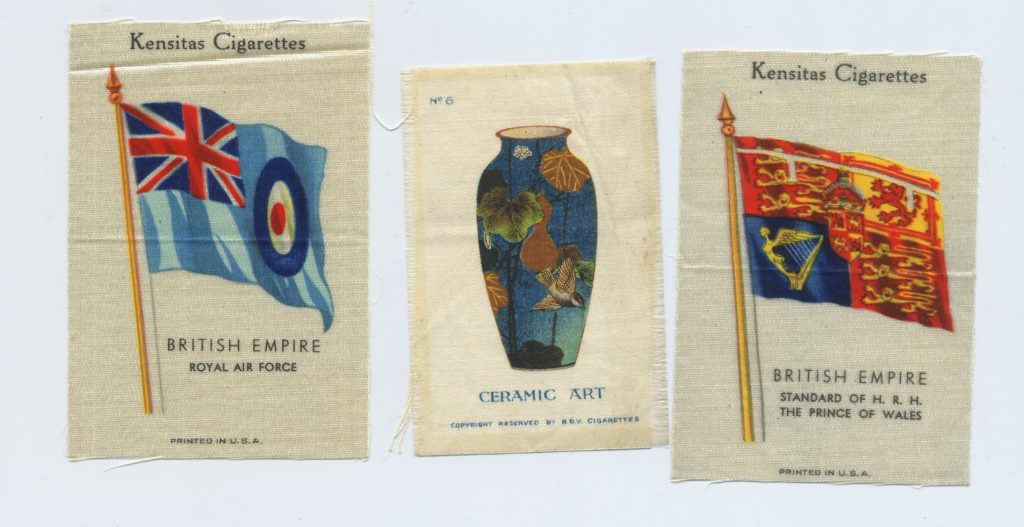 Three small silk cigarette cards. The left shows the british air force flag, the middle a ceramic pot, the right the flag of the prince of wales.