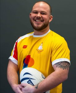 Portrait image of Jamie smiling in roundheads rugby kit, holding a rugby ball.