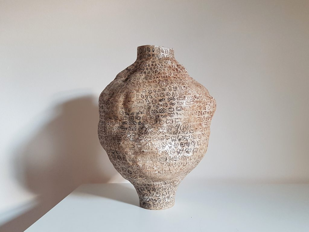Ceramic pot covered in small motifs and symbols