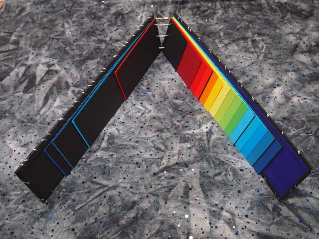 Narrow book of bright coloured pages in rainbow shades