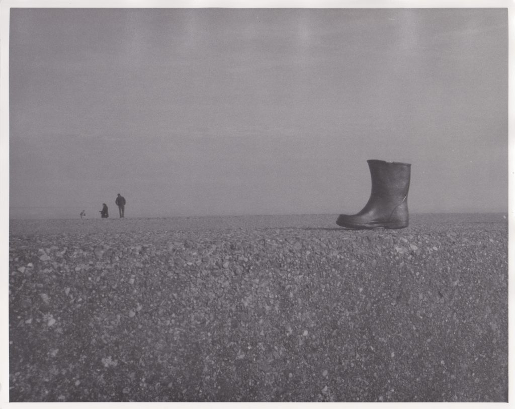 Mixed media work of a single boot on the sand