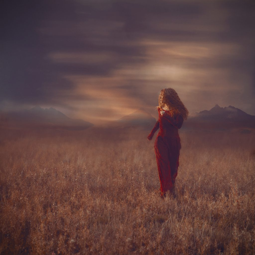 Digital print of a woman in a red dress within a vast landscape