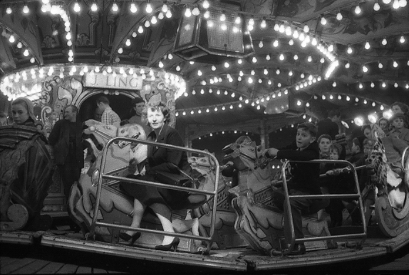 Black and white photograph of women on a carousel