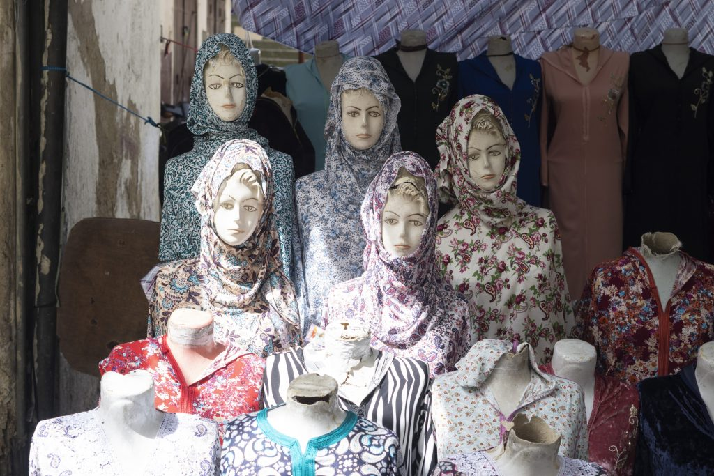 A digital print of mannequin heads, covered with patterned scarves and fabrics