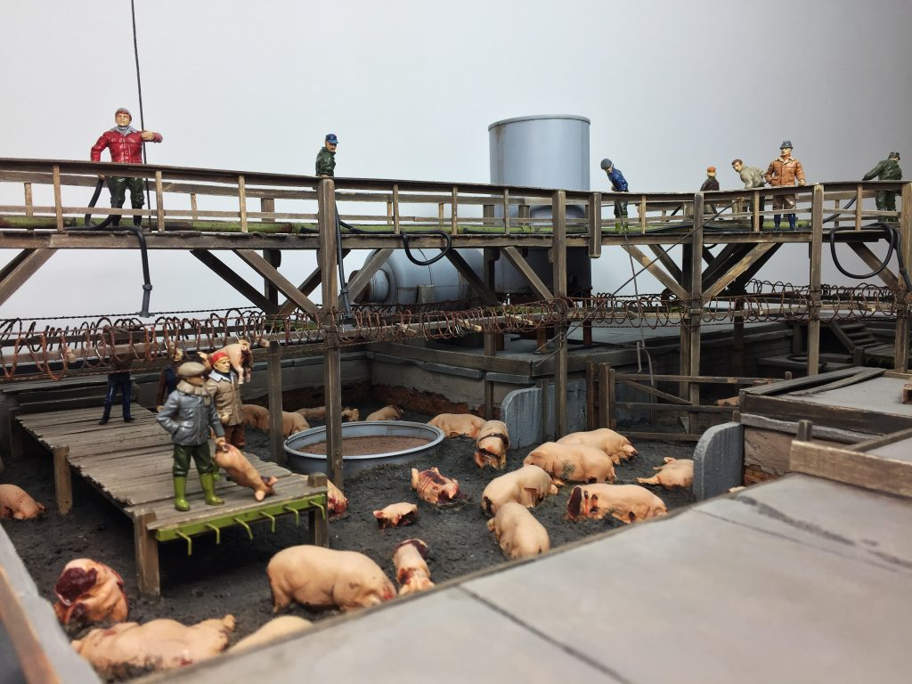 Mixed media work of a surreal pig farm – with miniature figures, pigs and meat