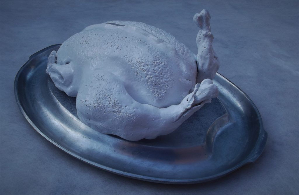 Mixed media work of a white cooked chicken on a metal platter