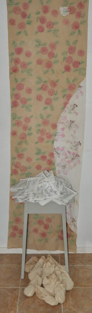 Sculptural work incorporating a floral wall paper hanging, and a wooden stool of textile books and shoes