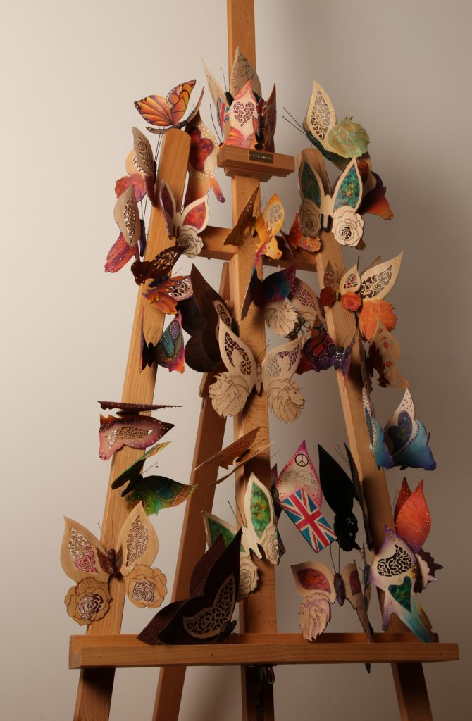Wood sculpture of colourful butterflies on a wooden easel