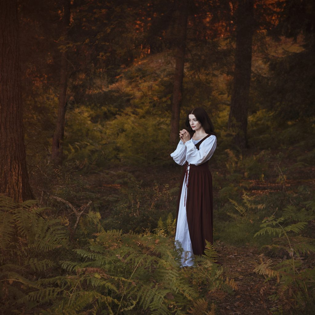 Digital print of a woman in a long dress stood in a wooded landscape