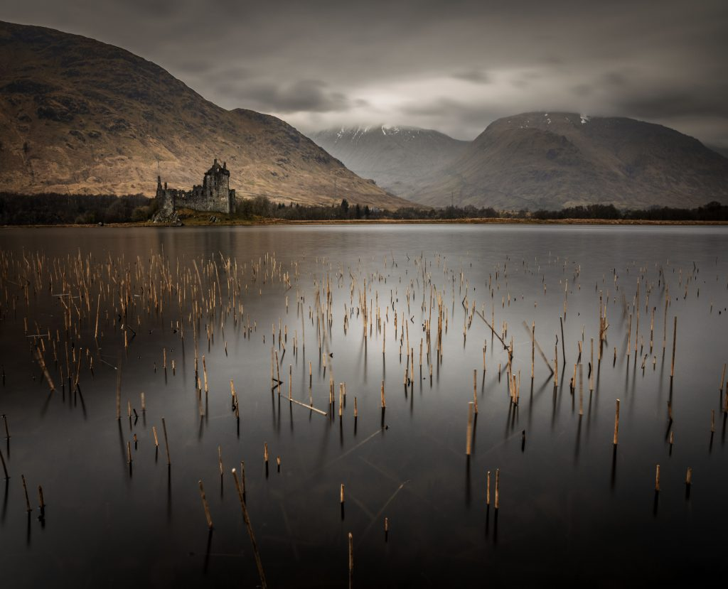 Digital print of castle, viewed across a lake – on a cloudy day