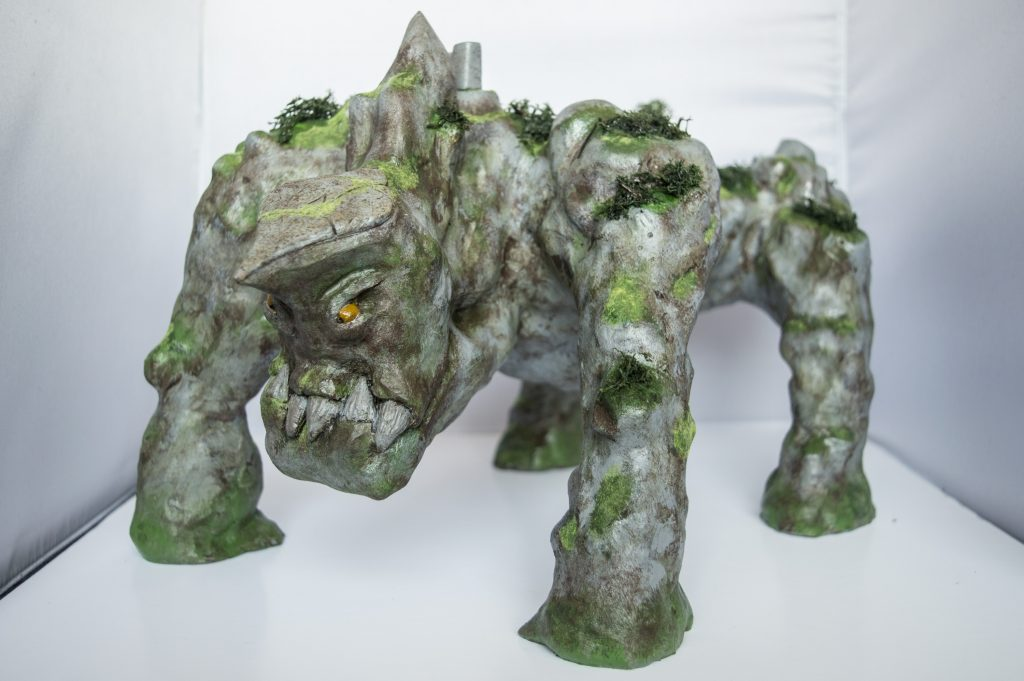 Mixed media sculpture of a moss-covered stone creature