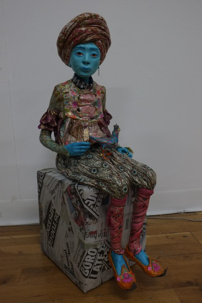 Mixed media sculpture of a blue-skinned seated figure in brightly patterned clothes, holding a bird