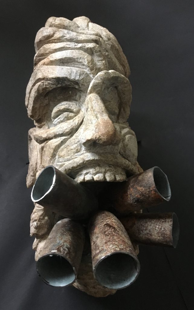 Stone sculpture of a face, with metal tubes in the mouth