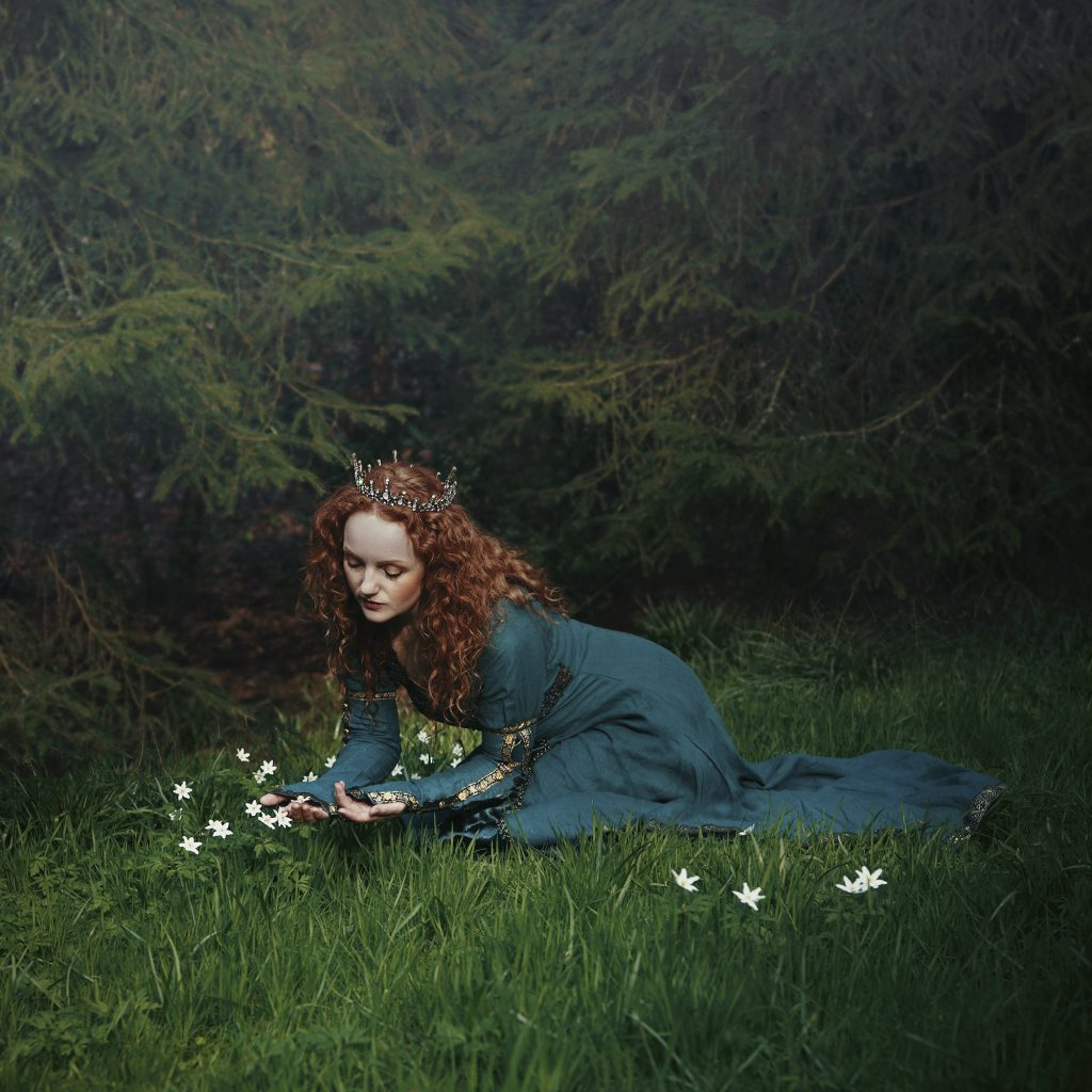 A digital print of a woman in an emerald dress, sat on the grass admiring the daisies.